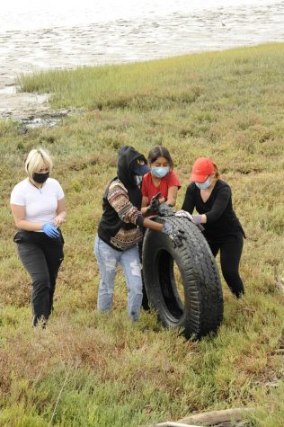 Student volunteers rolling a wheel they found up a hill to clean the baylands. (Photo courtesy of Linda Filo)